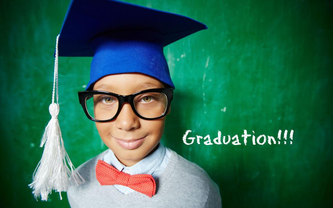 boy wearing graduation hat in front of chalkboard